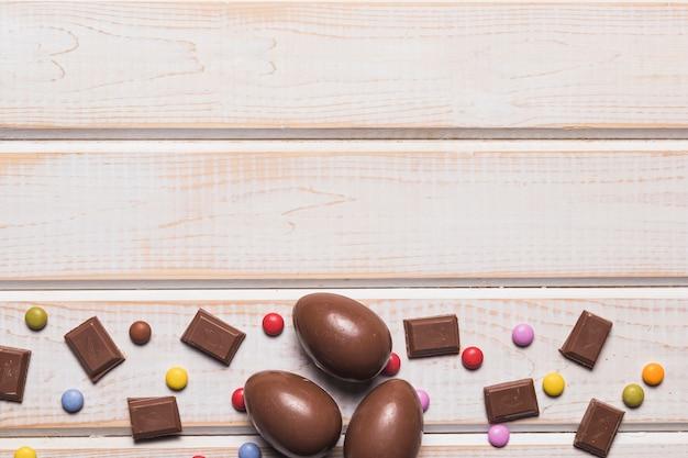 Trozos de chocolate; huevos de pascua y caramelos de gemas en el fondo del escritorio de madera.
