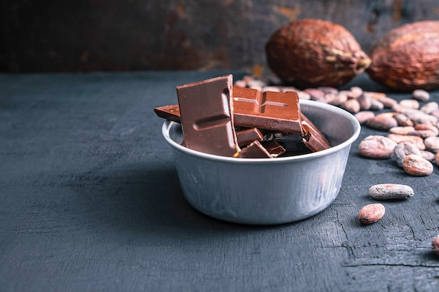 Trozos de chocolate negro y granos de cacao en mesa