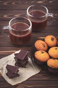 Trozos de chocolate negro, magdalenas y dos tazas con bebida de chocolate caliente en una pared de tablas de madera marrón. el concepto de desayuno romántico. bebidas y dulces, repostería y bebidas, por la mañana.