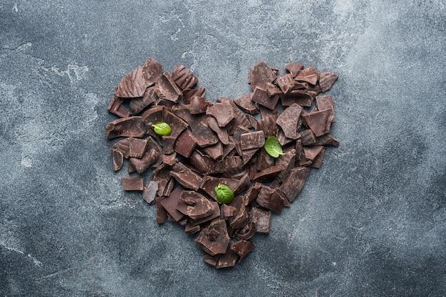 Trozos de chocolate oscuro machacado con hojas de menta en forma de corazón sobre un fondo de textura oscura.