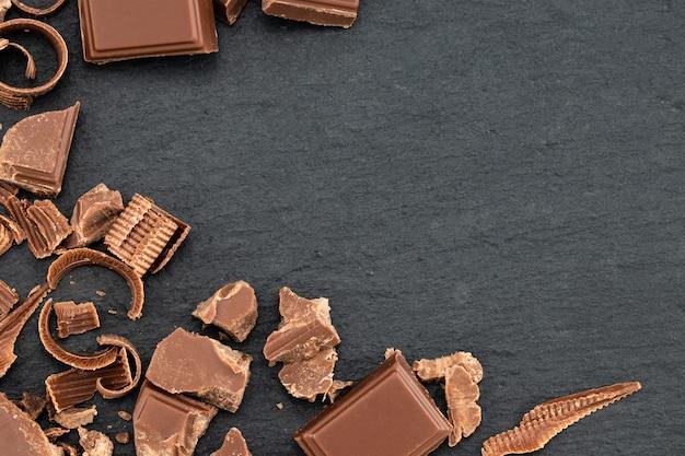 Trozos de chocolate rotos y virutas de chocolate en un oscuro