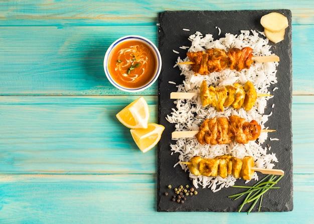 Trozos de cítricos y salsa cerca de pollo kebab