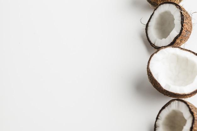 Trozos de coco maduro sobre fondo blanco, espacio de copia