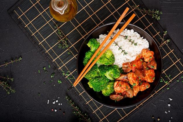 Trozos de filete de pollo con champiñones guisados en salsa de tomate con brócoli hervido y arroz. nutrición apropiada. estilo de vida saludable. menú dietético vista superior