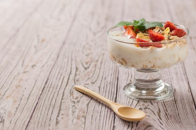 Trozos de fresas frescas en yogur con menta sobre una mesa de madera. comida natural deliciosa, sana y nutritiva.