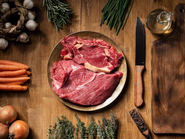 Trozos frescos de carne roja en plato vintage con diferentes verduras en la mesa de madera. vegetales frescos. zanahorias naranjas.