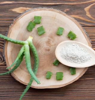 Trozos de hojas de aloe vera en posavasos de madera