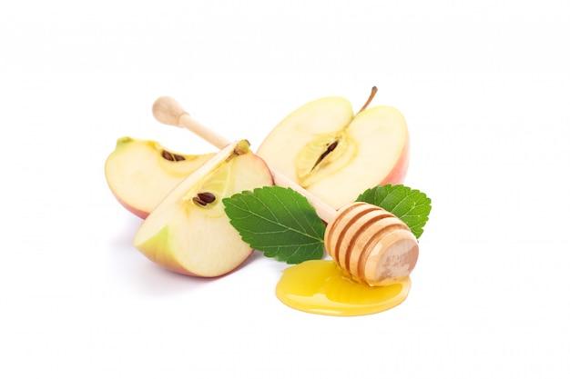Trozos de manzana, hojas y cazo con miel aislado en blanco