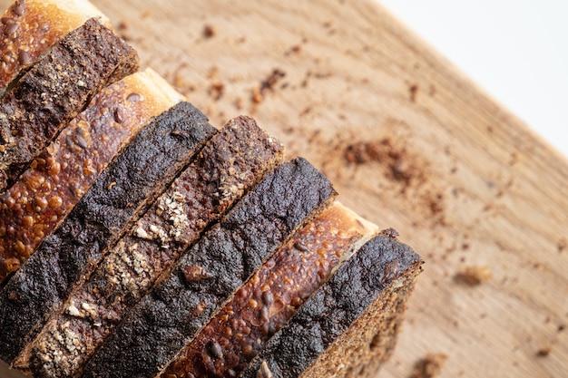 Trozos de pan integral en una tabla de cortar, disparados desde arriba