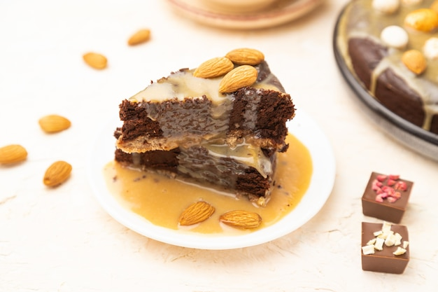 Trozos de pastel de brownie de chocolate con crema de caramelo y almendras sobre un fondo de hormigón blanco.