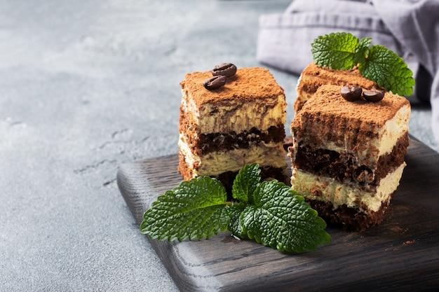 Trozos de pastel de tiramisú con crema delicada, granos de café y hojas de menta. mesa de hormigón oscuro con espacio de copia.