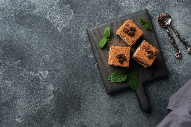 Trozos de pastel de tiramisú con crema delicada, granos de café y hojas de menta. vista superior.