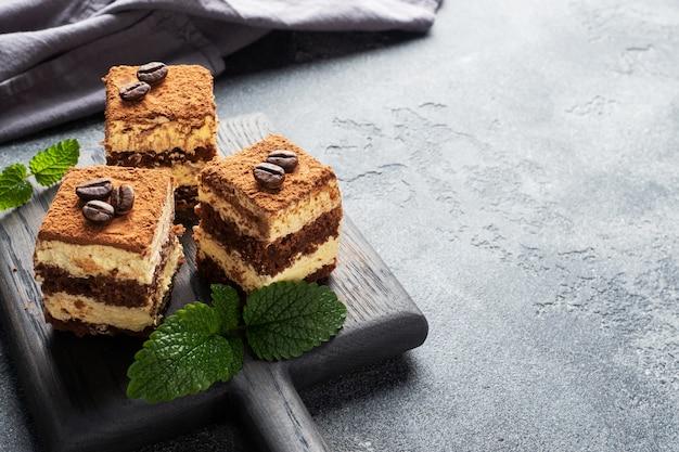 Trozos de pastel de tiramisú con crema delicada, granos de café y hojas de menta.