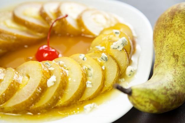 Trozos de pera en almíbar de naranja con queso dorblu en un plato blanco