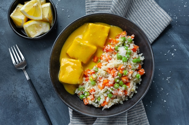 Trozos de pescado cocido con verduras crudas y salsa de curry servido en un bol. de cerca.