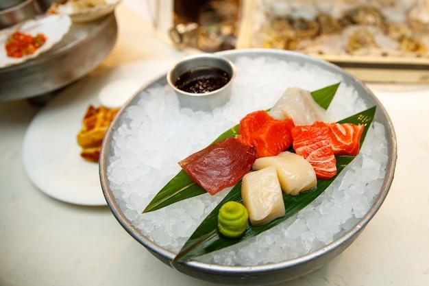 Trozos de pescado crudo en una bandeja con hielo.