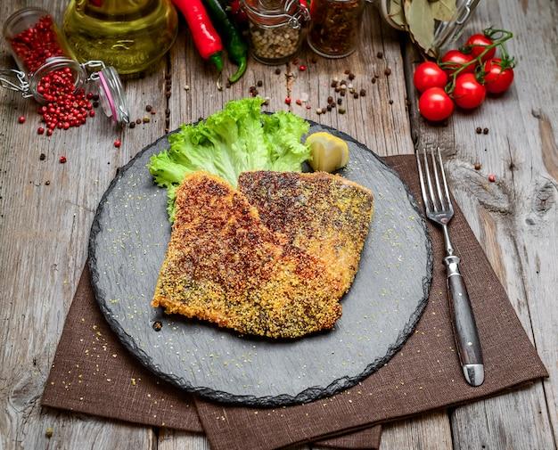 Trozos de pescado frito en un plato de cerámica sobre una superficie de madera oscura.