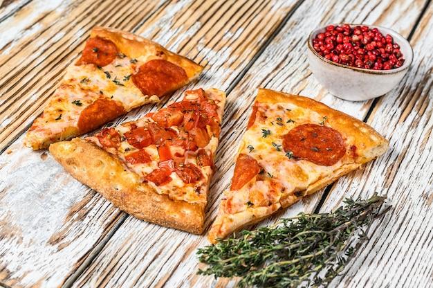 Trozos de pizza de pepperoni y tomate