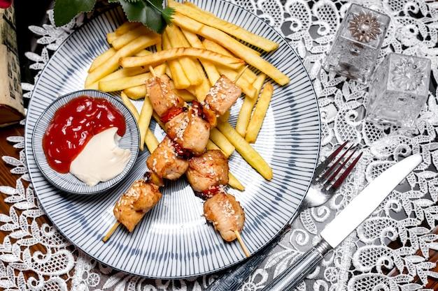 Trozos de pollo en brochetas servidos con papas fritas, mayonesa y salsa de tomate