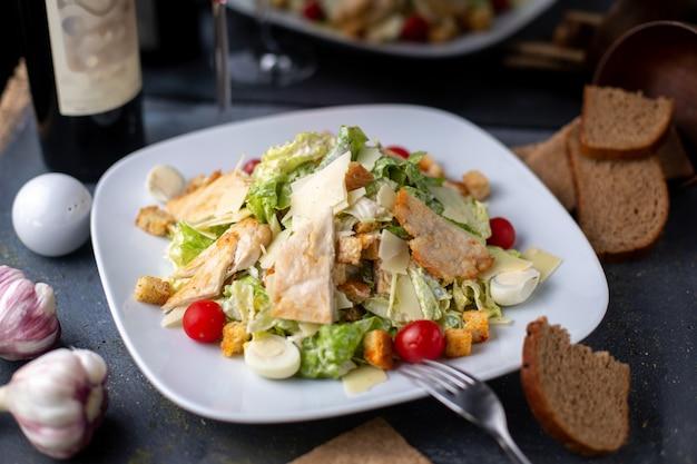 Trozos de pollo en rodajas junto con verduras frescas vino tinto dentro de un plato blanco