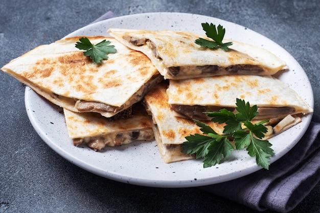 Trozos de quesadilla con crema agria de champiñones y queso