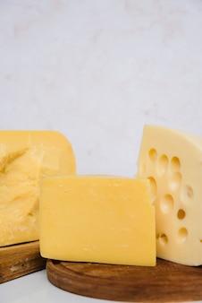 Trozos de queso emmental y gouda sobre tabla de madera.