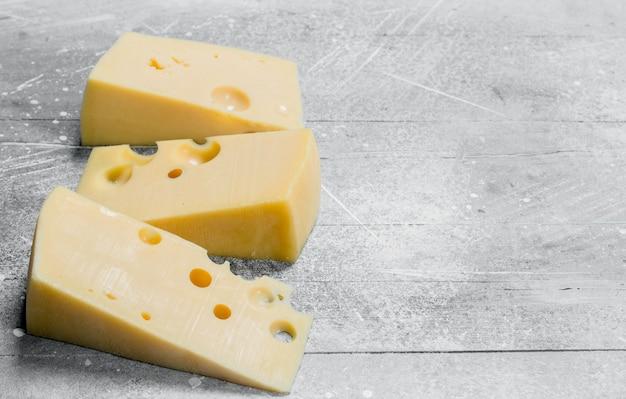 Trozos de queso fresco. sobre una mesa rústica.