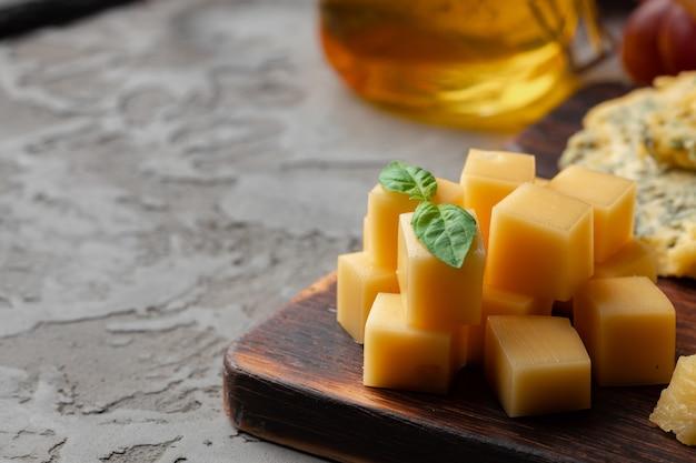 Trozos de queso y tarro de miel servido en mesa oscura