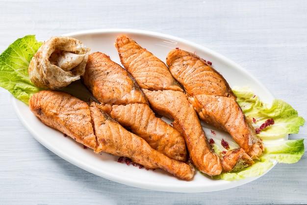 Trozos de salmón a la plancha en un plato blanco con ensalada y panqueque