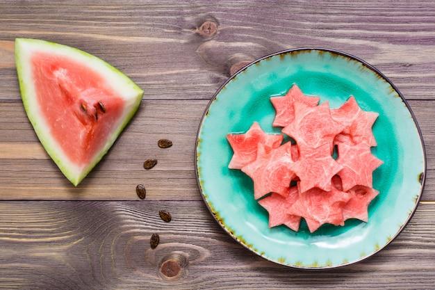 Trozos de sandía en forma de estrellas en un plato de cerámica y un gran trozo de sandía en una mesa de madera vista superior