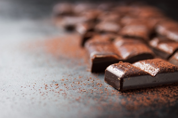 Trozos de tableta de chocolate sobre una mesa de madera negra y cacao espolvoreado encima