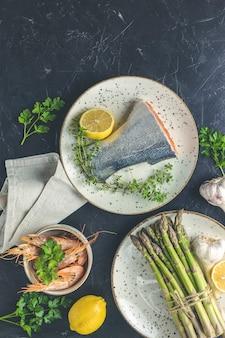 Trucha pescado rodeado de perejil, limón, camarones, gambas, espárragos en platos de cerámica. superficie de la mesa de hormigón negro. fondo de mariscos saludables.