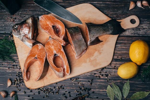 Trucha en rodajas en mesa de madera con limón y condimentos
