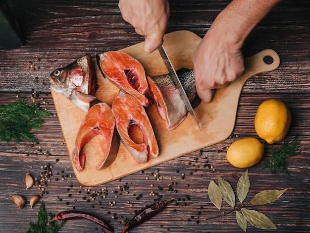 Trucha en el tablero cortada por un cocinero con un cuchillo