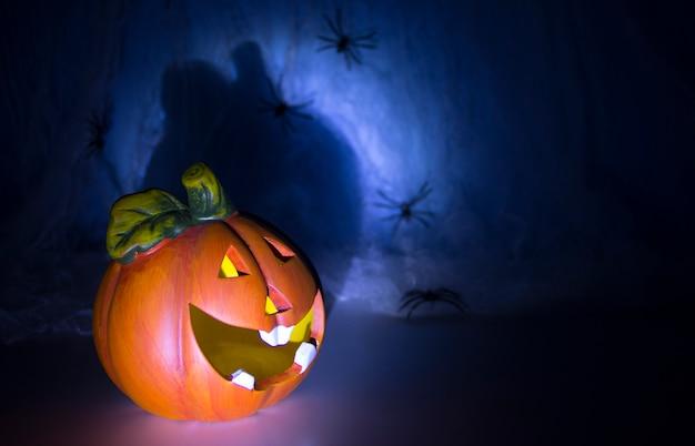 Truco o trato skull head y halloween pumpkin head of horrors frotar está cubierto con una telaraña