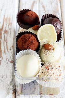 Trufas de chocolate en una caja de cristal sobre un fondo blanco vintage. bolas caseras de energía fresca. regalo de san valentín, cumpleaños