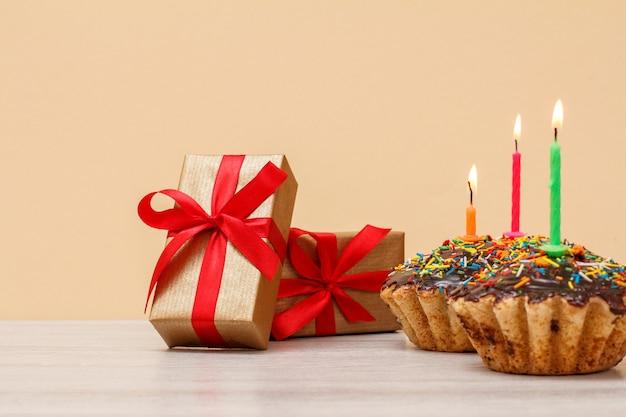 Ttree muffin de cumpleaños sabroso con glaseado de chocolate y caramelo, decorado con velas festivas encendidas y cajas de regalo con cintas rojas sobre fondo beige. feliz cumpleaños concepto mínimo.