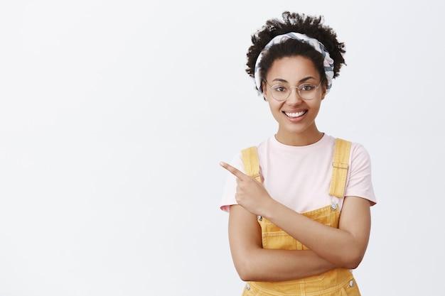 Tu camino hasta allí. retrato de afroamericano confiado y feliz de aspecto amistoso con gafas, diadema de moda y monos amarillos, apuntando a la esquina superior izquierda y sonriendo alegremente sobre la pared gris