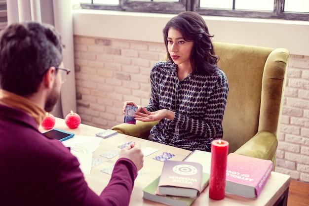 Tu firma. bonita mujer atractiva apuntando a la tarjeta mientras habla con su cliente