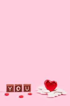 Tu inscripción en trozos de chocolate y adorno de corazón.