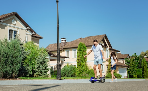 A tu lado. adorable niña sosteniendo la mano de su padre y siguiéndolo mientras él montaba un scooter de autoequilibrio por la calle