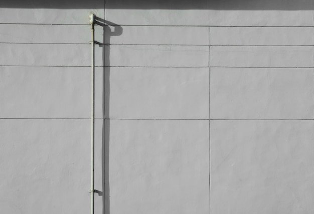 Tubería de acero vieja con la sombra en la pared gris del cemento.