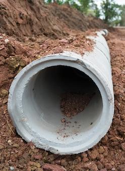 Tubería de drenaje de concreto en un sitio de construcción. tubería de concreto, sistema de aguas residuales apiladas.