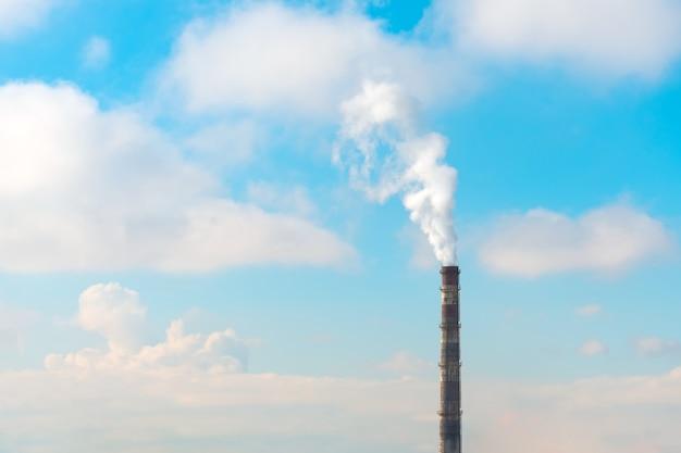 Tubería con emisiones de humo durante el tiempo soleado con nubes.