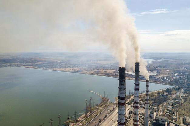 Tuberías altas de planta de energía, humo blanco en paisaje rural, agua de lago y espacio de copia de cielo azul.
