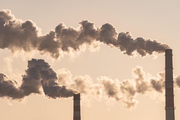 Las tuberías de las centrales eléctricas emiten humo nocivo al aire. contaminación, calentamiento global