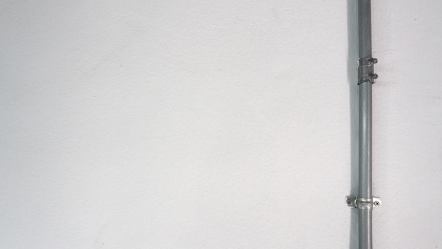 Tubo de acero plateado viejo y pared de textura blanca y sombra.