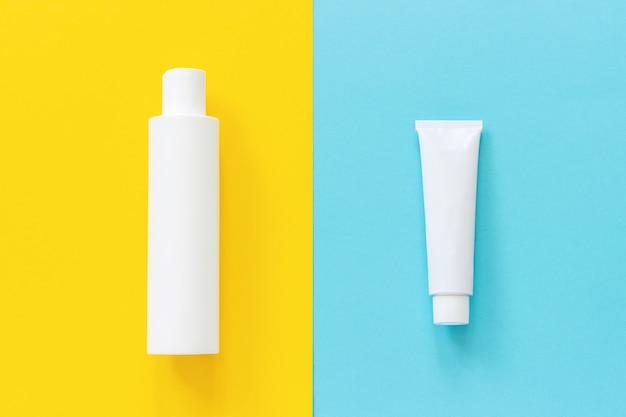 Tubo blanco y botella de protector solar u otro producto cosmético sobre fondo amarillo y azul