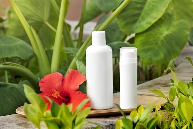 Tubo blanco vacío de botella de cuidado de la piel en placa de bambú