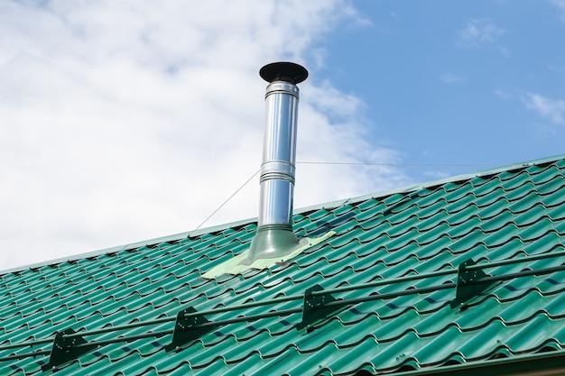 Tubo de chimenea de metal de acero inoxidable en el techo de la casa contra el cielo